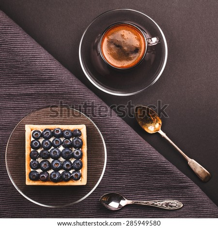 Delicious fruit tartlet with cup of coffee on a dark background - stock photo