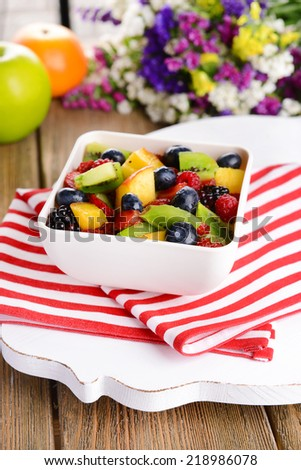 Delicious fruits salad in plate on table close-up - stock photo