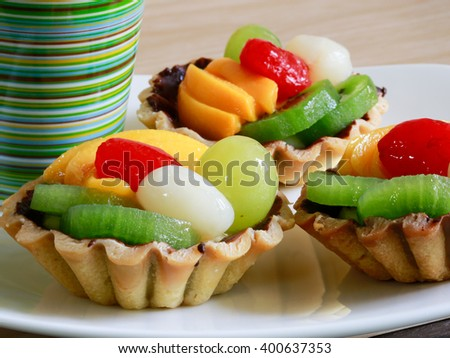 Delicious fruits tarts with kiwi, peach, strawberry, lychee, grape on top and a white cup of tea