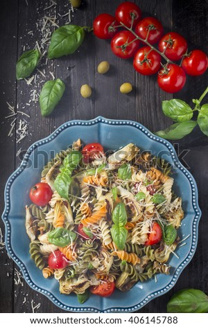 Delicious fusilli pasta with artichokes, cherry tomatoes, fresh basil and parmesan cheese on a black background - stock photo