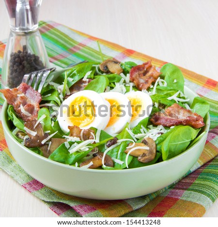 Delicious, generous and fresh salad with spinach, bacon, champignon mushrooms, cheese and boiled eggs with bright yolk - stock photo