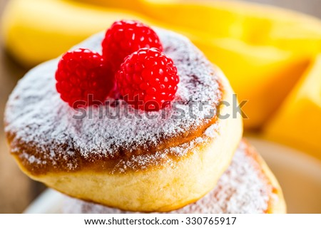 delicious german doughnuts powdered with sugar and raspberry on the top