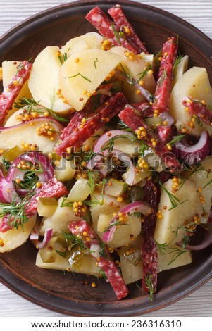 delicious German potato salad on a plate close-up view from above vertical  - stock photo