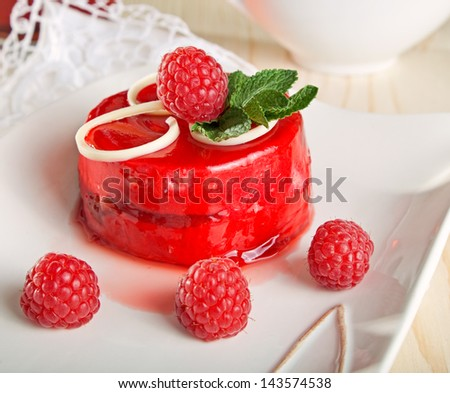 Delicious glazed cake decorated with raspberries and mint. - stock photo