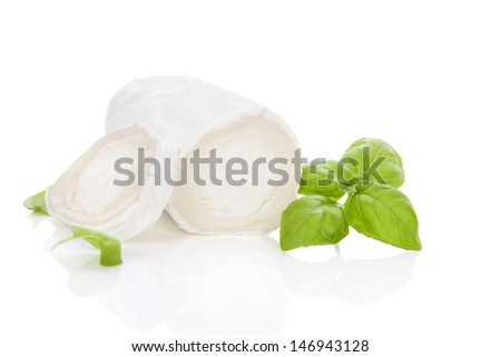 Delicious goat cheese slices and piece with fresh basil leaves isolated on white background. Luxurious culinary cheese still life. - stock photo