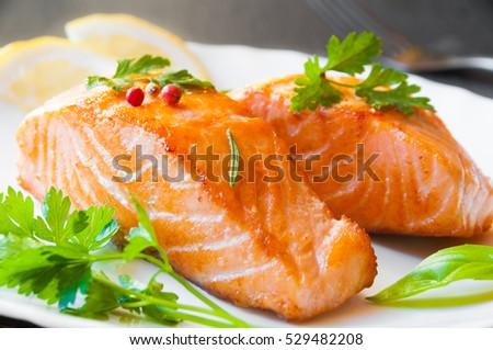 Delicious golden cooked salmon fillet with herbs and lemon