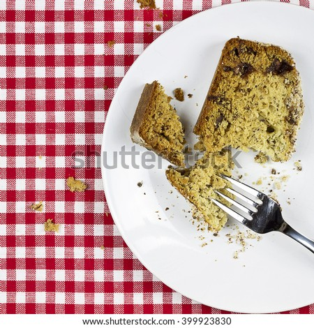 Delicious golden loaf of homemade baked banana fruit bread on table setting. - stock photo
