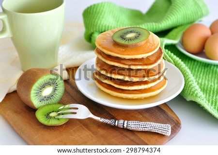 Delicious golden pancakes cooked on dry pan and served for breakfast with honey and kiwi fruit on a wooden board. Still life, copy space, green yellow shades - stock photo