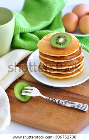 Delicious golden pancakes cooked on dry pan and served for breakfast with honey and kiwi fruit on a wooden board. Healthy eating lifestyle, still life, copy space - stock photo