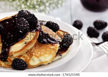 Delicious golden pancakes with fresh blackberries and blackberry jam. Extreme shallow depth of field. - stock photo