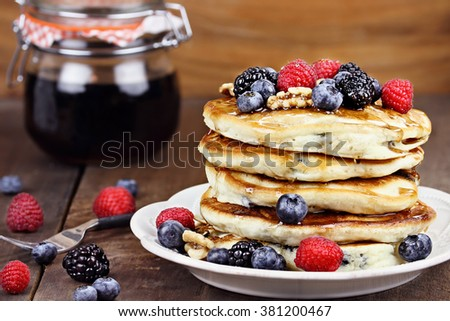 Delicious golden pancakes with fresh blackberries, raspberries, blueberries and sweet maple syrup. Extreme shallow depth of field.