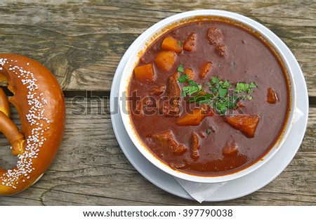Delicious Goulash soup, made with potatoes and meat  braised in tomato sauce with pretzel on the wooden bench of a beer garden, traditional seasonal open air restaurant, typical Bavarian.
