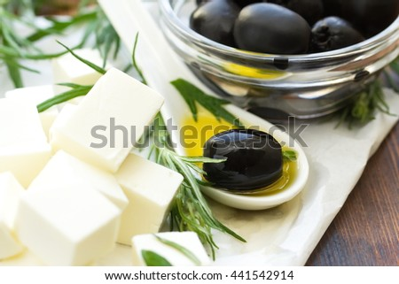 Delicious Greek feta cheese with black olives and olive oil - stock photo
