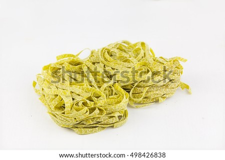 delicious green tagliatelle isolated on white background