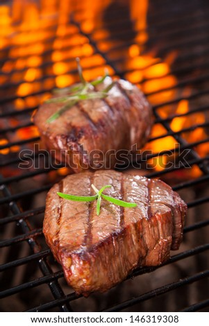 Delicious grilled beef steak with fire on background - stock photo