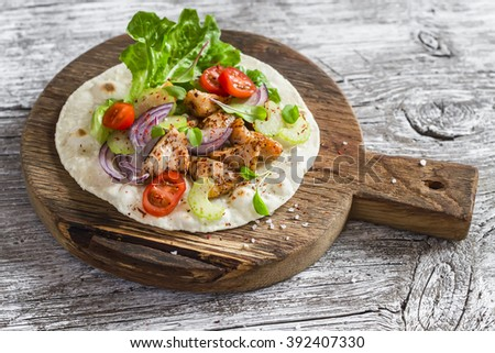 Delicious grilled chicken and fresh vegetables homemade tortilla on a rustic cutting board on a light wooden background - stock photo