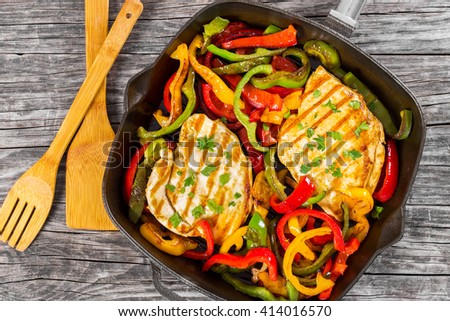 Delicious Grilled Chicken breast fillet and fried bell pepper on a pan on an old rustic table, horizontal top view - stock photo