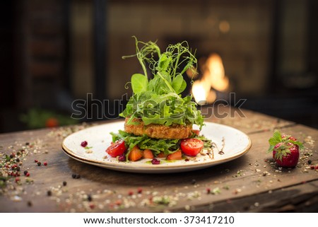 Delicious grilled coat cheese salad served on a wooden table with strawberries, fireplace on background - stock photo