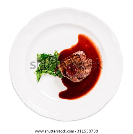 Delicious grilled fillet mignon steak with chard covered with red wine sauce. Isolated on a white background. - stock photo