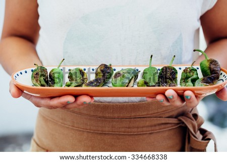 Delicious grilled green peppers on a plate ready to be served - stock photo