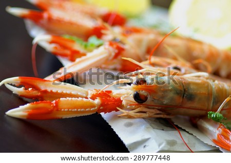 Delicious Grilled Langoustines  on Newspaper closeup on Dark Wooden background. Focus on Animal Eyes