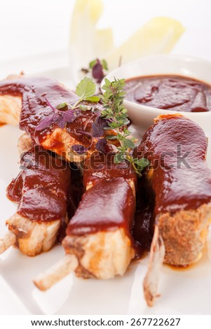 Delicious grilled pork ribs served with a rich brown gravy or BBQ sauce garnished with fresh herbs , close up side view
