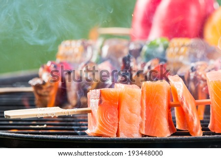 Delicious grilled salmon skewers on fire