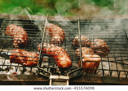 delicious grilled sausages roasting on grates with flames and smoke, bbq outdoors at summer picnic, camping concept - stock photo