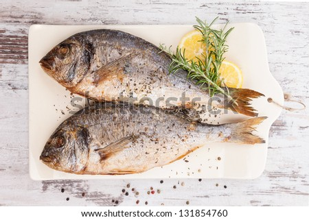 Delicious grilled sea bream fish on kitchen board with rosemary, lemon and colorful peppercorns on white textured wooden background. Culinary healthy cooking. - stock photo