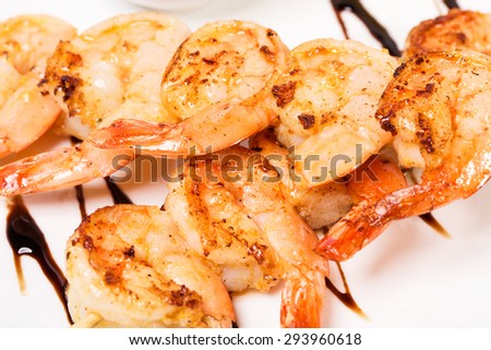 Delicious grilled shrimps on skewers covered with dark soya sauce. Macro. Photo can be used as a whole background. - stock photo