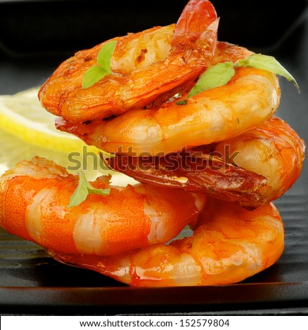 Delicious Grilled Shrimps with Lemon and Thyme closeup on Black plate - stock photo