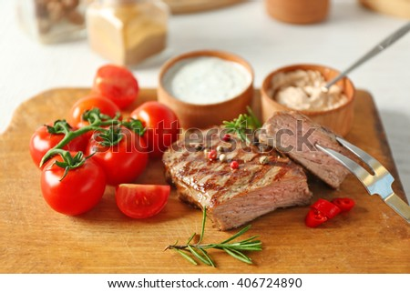 Delicious grilled steak on cutting board, closeup - stock photo