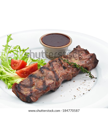Delicious grilled steak served with blood sauce and vegetables. Isolated on white
