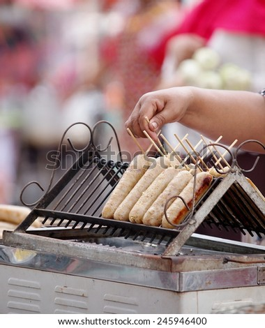 delicious grilled THAI traditional north-east or ISAN style sausages with rice and pork for sale on a street market in THAILAND - stock photo