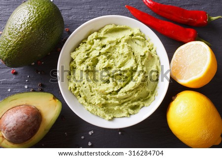 Delicious guacamole sauce and ingredients close-up on the table. Horizontal top view - stock photo