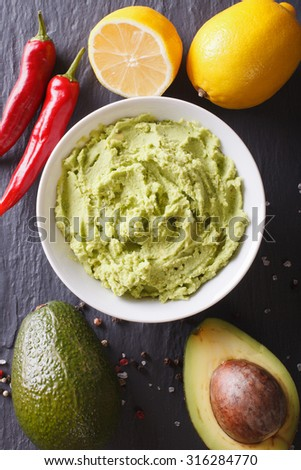 Delicious guacamole sauce and ingredients close-up on the table. vertical top view - stock photo