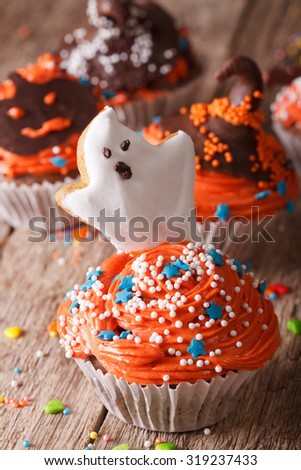 Delicious Halloween cupcakes with a spooky on a table close-up. Vertical