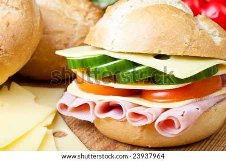 Delicious ham, cheese and salad sandwich on a wooden board