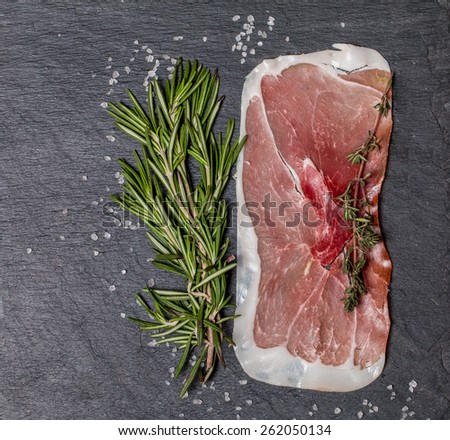 Delicious ham slices with rosemary and salt on black background, top view - stock photo