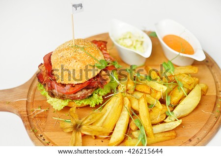 Delicious hamburger and french fries isolated on white background. Hamburger, french fries, sauce on a wooden tablet. Hearty snack: a hamburger and fries. - stock photo