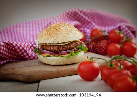 Delicious hamburger in rustic setting. Burger on wooden board with beer - stock photo