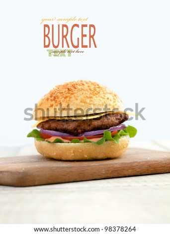 Delicious hamburger isolated on white with copyspace. Burger on wooden board