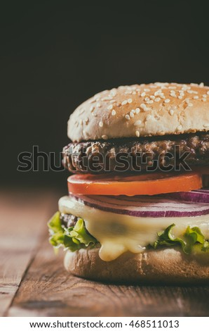 Delicious hamburger on dark wooden background - close-up