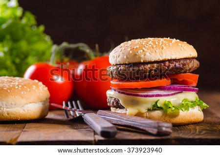 Delicious hamburger on dark wooden background with extra bun and - stock photo