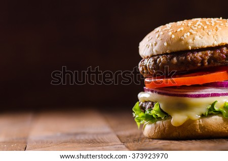 Delicious hamburger on dark wooden background with negative space