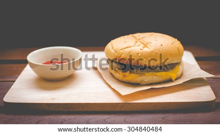 Delicious hamburger on wood, retro and vintage tone.