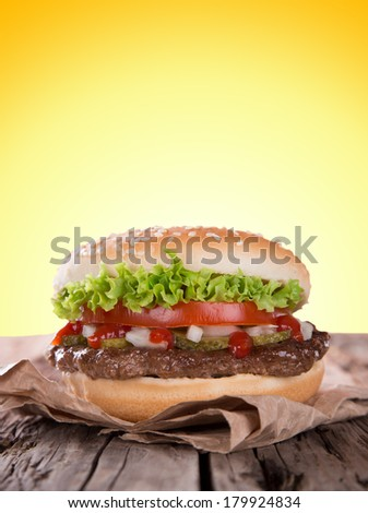 Delicious hamburger on wooden background - stock photo