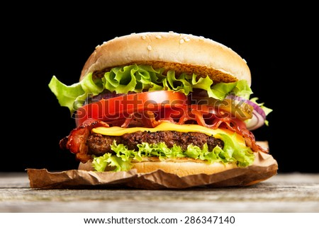Delicious hamburger on wooden background