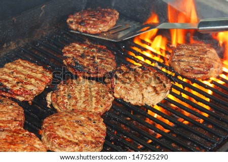 Delicious hamburger patties on a metal grill with fire under - stock photo