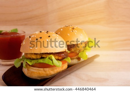 Delicious hamburger served on wooden planks with sauce on sunshine wooden background